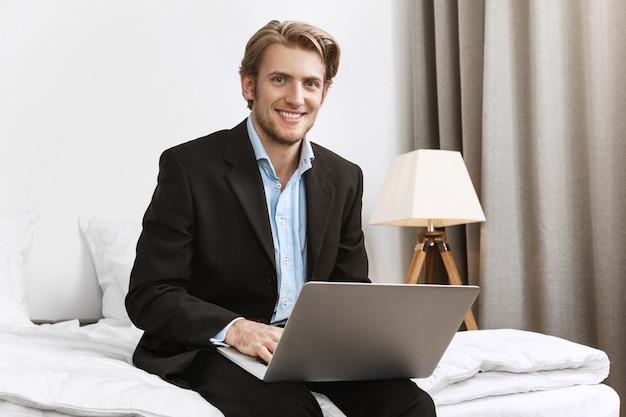 Ritratto di allegro direttore della società barbuto in elegante abito nero, sorridendo brillantemente, lavorando su un computer portatile in camera d'albergo confortevole durante il viaggio d'affari.