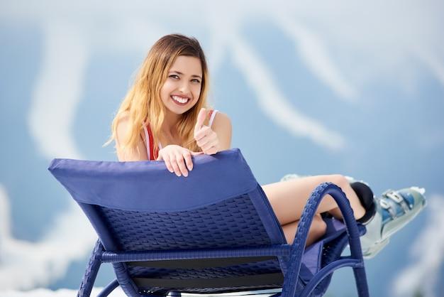 Ritratto di allegro sciatore giovane donna che indossa corpetto rosso, sorridendo alla telecamera, mostrando il pollice in alto, godendo su una sedia a sdraio blu presso la stazione sciistica. stagione sciistica e concetto di sport invernali