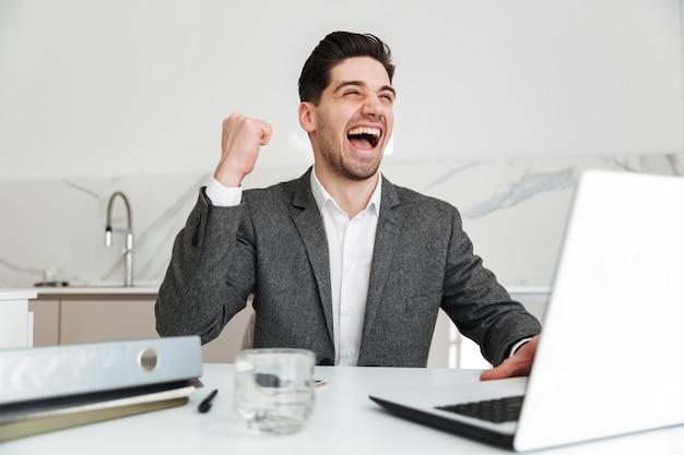 Ritratto di allegro uomo d'affari allegro esultando e stringendo il pugno mentre era seduto in ufficio e lavorando su un computer portatile
