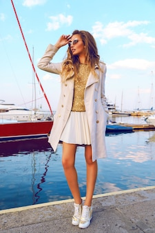Ritratto di alta moda della bellissima modella con capelli ombre arricciati alla moda, accogliente cappotto di lana color crema autunnale, top dorato e occhiali da sole, incredibile whew sul porto e yacht club.
