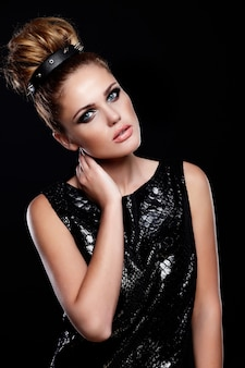 Ritratto di alta moda look.glamor di bello modello femminile giovane donna caucasica alla moda sexy in vestito nero con trucco e l'acconciatura luminosi