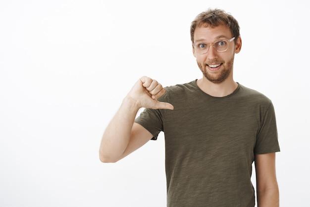 Ritratto di ambizioso collega di bell'aspetto maschio in maglietta verde scuro che punta a se stesso mentre si offre volontario per essere candidato sorridendo con gioia