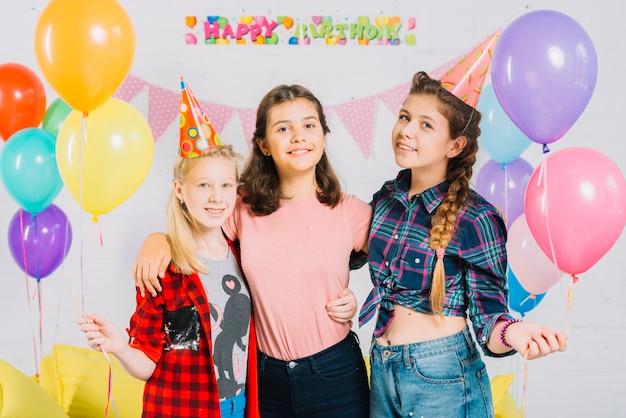 Ritratto di amici felici che tengono palloncini colorati
