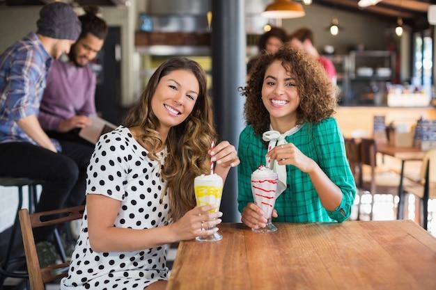 Ritratto di amici femminili felici che tengono i frullati nel ristorante