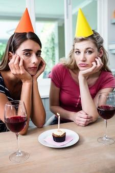 Ritratto di amici tristi seduto al tavolo durante la festa di compleanno