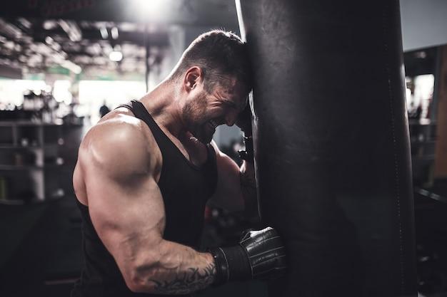 Ritratto di angolo basso di giovane uomo stanco di sport che si appoggia sul sacco da boxe