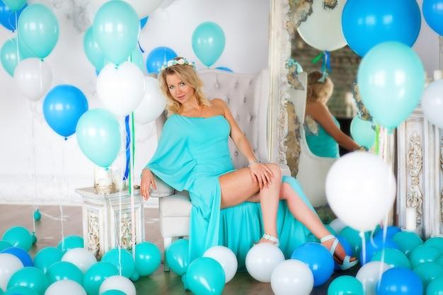 Ritratto di attraente giovane donna in abito blu alla festa con palloncini