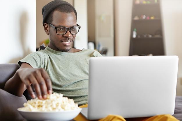 Ritratto di attraente giovane maschio africano singolo in occhiali avendo riposo in casa, seduto sul divano grigio con un pc portatile in grembo, guardando lo schermo con interesse, leggendo e-book e mangiando popcorn