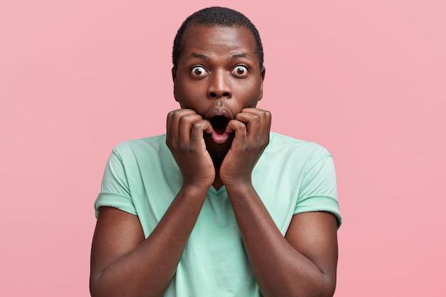 Ritratto di attraente maschio dalla pelle scura guarda con gli occhi spuntati fuori, tiene la bocca ampiamente aperta, vestito con una maglietta casual, pone contro il rosa