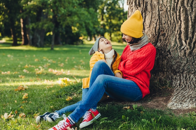 Ritratto di attraente modello femminile, ha una piacevole conversazione con la figlia, riposo sull'erba verde