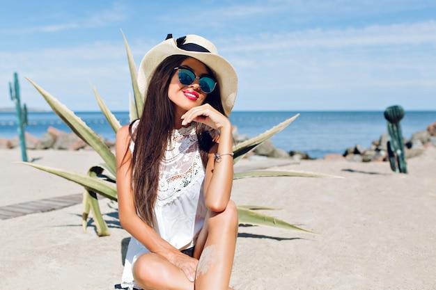 Ritratto di attraente ragazza bruna con capelli lunghi seduto sulla spiaggia vicino a cactus sullo sfondo. sta sorridendo alla telecamera.