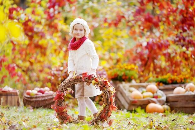 Ritratto di autunno della bambina sveglia. bambina graziosa con ghirlanda di foglie di vite rossa nella sosta di autunno.