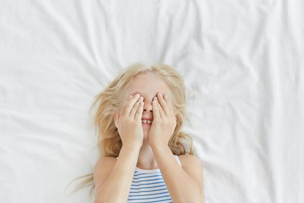 Ritratto di bambina adorabile con i capelli chiari, coprendosi gli occhi con le mani mentre si diverte e si nasconde da qualcuno, ridendo, sdraiato su lenzuola bianche. bambino spensierato svegliarsi la mattina