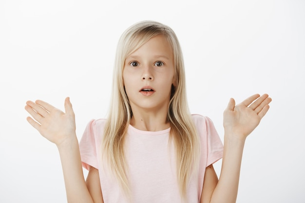 Ritratto di bambina adorabile confusa e preoccupata con i capelli biondi, trattenendo il respiro e fissando scioccata, alzando i palmi verso l'alto, essendo sorpreso o stupito dalla situazione confusa sul muro grigio