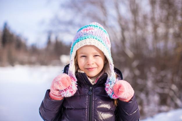 Ritratto di bambina adorabile in cappello di inverno nella foresta nevosa