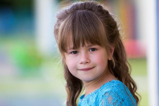 Ritratto di bambina bionda alla moda in abito blu, con occhi grigi e bei capelli lunghi