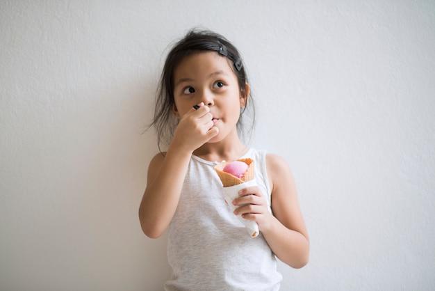 Ritratto di bambina che mangia il gelato con buona sensazione