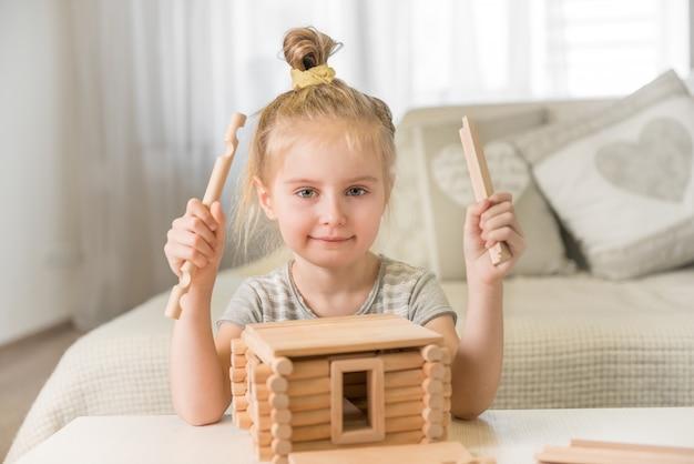 Ritratto di bambina con modello di casa.