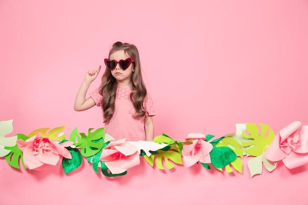 Ritratto di bambina con occhiali da sole a forma di cuore su sfondo rosa con fiori di carta, posto per il testo, concetto di pubblicità estiva