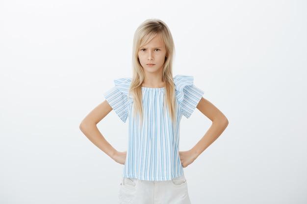 Ritratto di bambina europea offesa dispiaciuta, tenendo le mani sui fianchi, accigliato e guardando da sotto la fronte, arrabbiato con l'amico che ha mangiato tutta la torta, in piedi deluso sul muro grigio