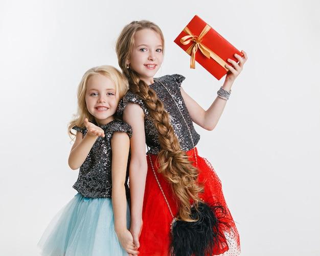 Ritratto di bambine con acconciatura riccia in piedi sulla festa in vestito, holdi