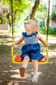 Ritratto di bambino 1-2 anni. ragazza caucasica felice del bambino che gioca i giocattoli al campo da giuoco. ragazza sorridente bambini e concetto di sport.