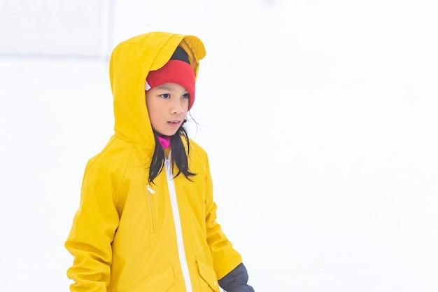 Ritratto di bambino asiatico gril in abbigliamento invernale giallo