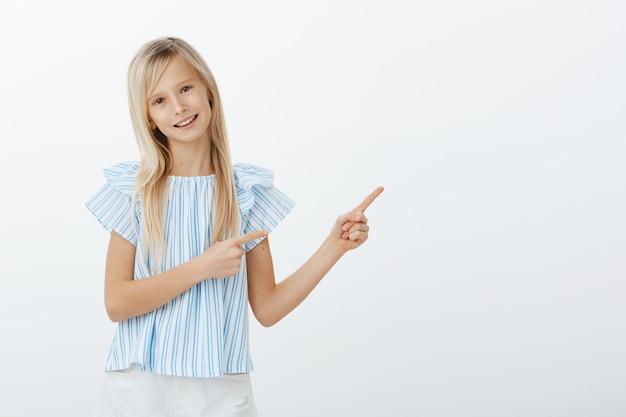 Ritratto di bambino biondo adorabile positivo in camicetta blu, indicando nell'angolo in alto a destra e sorridente con espressione amichevole compiaciuta, essendo di ottimo umore giocoso, chiedendo all'amico di giocare insieme