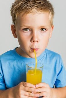 Ritratto di bambino che beve il succo