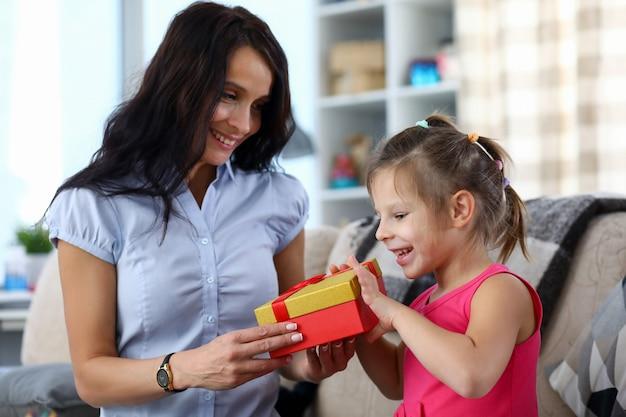 Ritratto di bambino felice prendendo presente dalla madre premurosa per le vacanze. mamma sorridente e figlia allegra che godono insieme del tempo. concetto di infanzia e genitorialità
