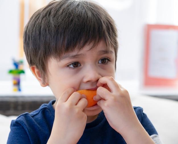 Ritratto di bambino sano mangiando pompelmo