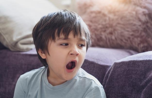 Ritratto di bambino stanco che sbadiglia seduto accanto al divano, ragazzo assonnato che sbadiglia e guarda in basso, bambino che ha allergia durante i cambiamenti climatici, l'infanzia ha la riflessione o la febbre da fieno dall'acaro della polvere, allergie nel bambino