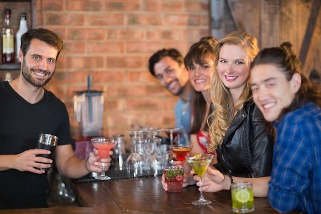 Ritratto di barista che serve bevande ai clienti felici