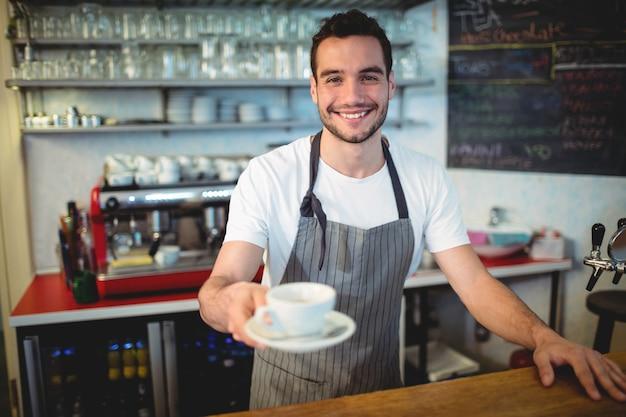 Ritratto di barista fiducioso che serve caffè al caffè