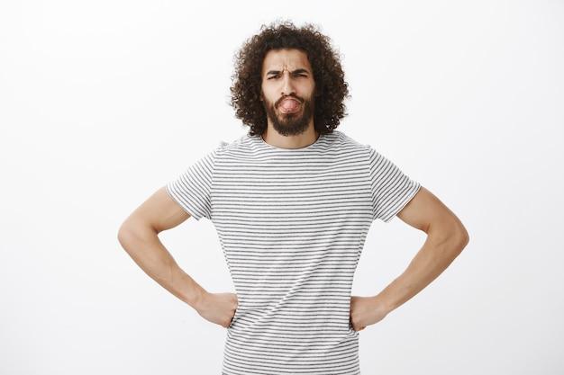 Ritratto di bel ragazzo barbuto spensierato in maglietta elegante, tenendo le mani sui fianchi con espressione fiduciosa, accigliato e linguetta