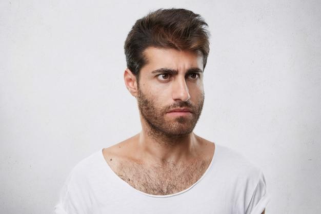 Ritratto di bel ragazzo con gli occhi marroni, pettinatura alla moda e barba che guarda seriamente da parte avendo espressione arrabbiata insoddisfatta