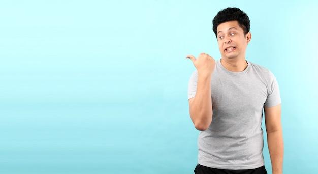 Ritratto di bel viso, shock e sorpresa di un uomo asiatico che punta il dito sullo spazio vuoto isolato sul muro blu.