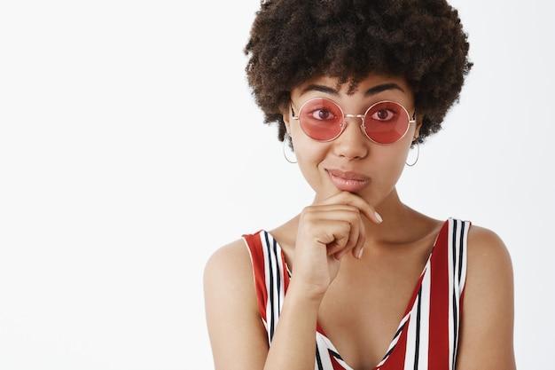Ritratto di bell'americano alla moda in occhiali da sole, tenendo la mano sul mento e sorridendo, pensando, gradendo il concetto interessante