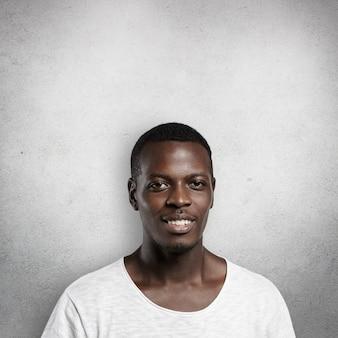 Ritratto di bell'uomo africano bello con l'espressione soddisfatta.