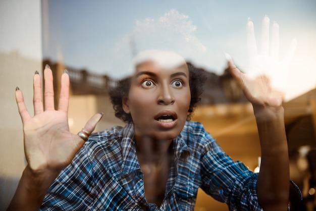 Ritratto di bella africana sorpresa dietro vetro che gioca scimmia. sparato dall'esterno.