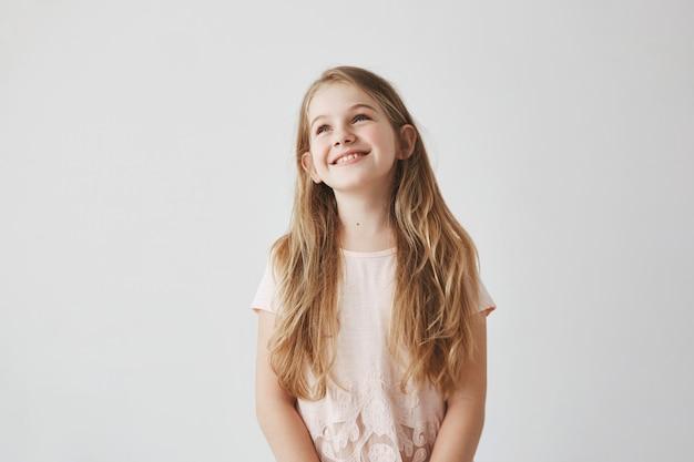 Ritratto di bella bambina bionda con gli occhi azzurri, essendo in gita scolastica nello zoo, guardando a lato giraffa con espressione faccia felice.