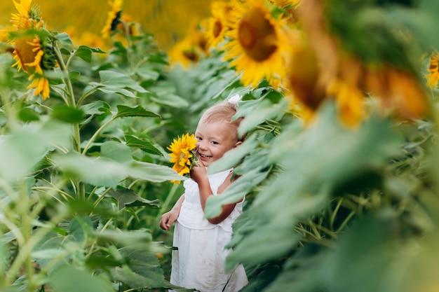 Ritratto di bella bambina sorridente, su sfondo di campo di girasole. messa a fuoco selettiva.
