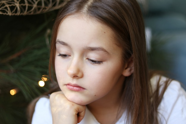 Ritratto di bella bambina triste che si siede sotto l'albero di natale decorato