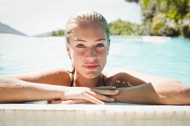 Ritratto di bella bionda in piscina appoggiata sul bordo