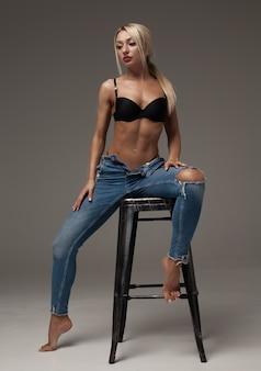 Ritratto di bella bionda sexy con una bella figura che indossa jeans di marca blu che ci mostrano la sua pancia allettante. isolato su sfondo grigio