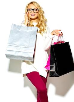 Ritratto di bella carina felice dolce donna bionda sorridente che tiene nelle sue mani grandi borse colorate per lo shopping in abiti hipster isolato su bianco