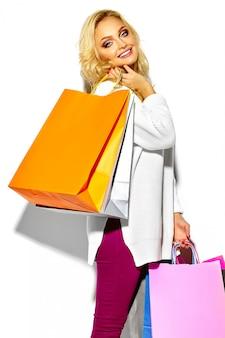 Ritratto di bella carina felice dolce donna bionda sorridente che tiene nelle sue mani grandi borse colorate shopping in abiti maglione hipster isolato su bianco