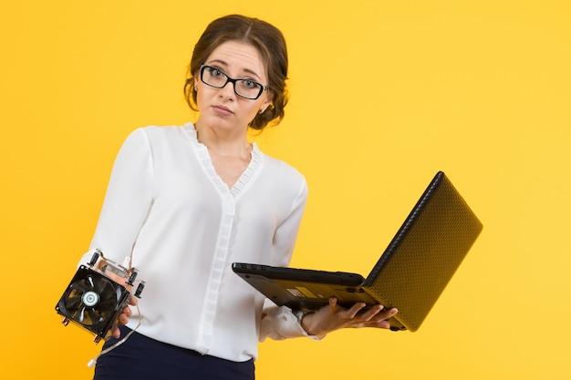 Ritratto di bella confusa bella confusa donna d'affari con il computer portatile sul giallo