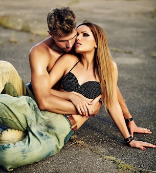 Ritratto di bella coppia. modello biondo alla moda sexy della giovane donna con trucco luminoso con pelle abbronzata perfetta e uomo muscoloso bello in jeans all'aperto sul fondo dell'asfalto