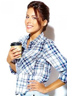 Ritratto di bella donna adolescente cool elegante in camicia a scacchi, tenendo la tazza di caffè in plastica
